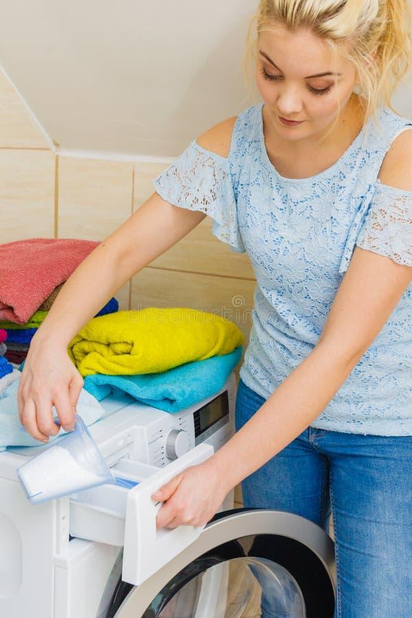 Flickan h?ller tvagningpulver in i maskinen arkivfoto