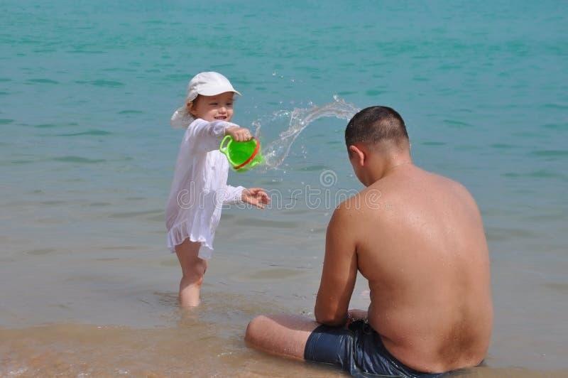 Flickan h?ller vatten p? hennes fader F?rgst?nk av vatten i havet Barn och fader p? semester royaltyfria bilder