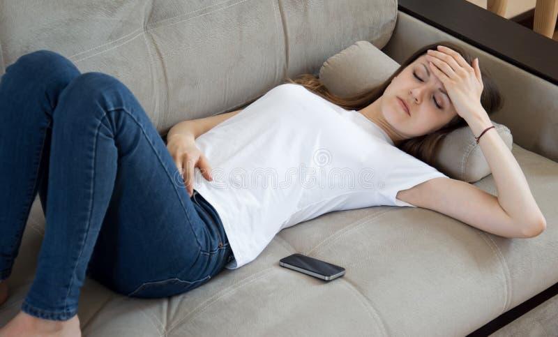 Flickan har en huvudv?rk Huvudv?rk migr?n Flickan ligger på soffan med en huvudvärk royaltyfria bilder