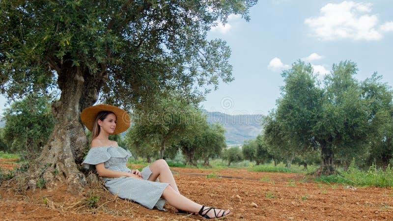 Flickan har en vila i grekisk olivträdgård arkivfoton
