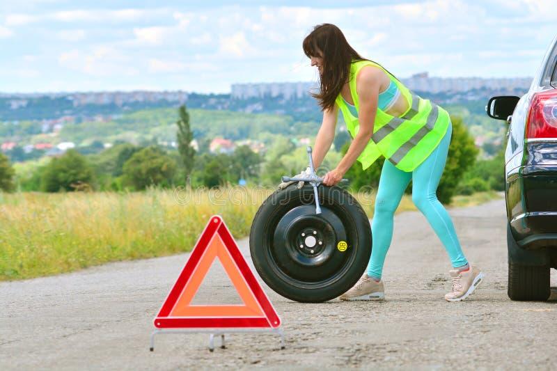 Flickan har ett problem med utbytet för det extra- hjulet royaltyfri foto