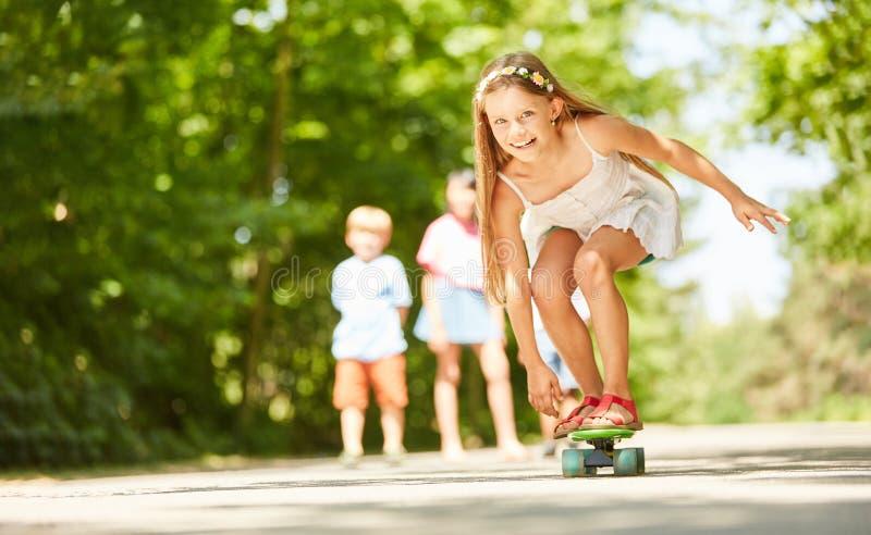 Flickan har gyckel, medan skateboarding royaltyfria bilder