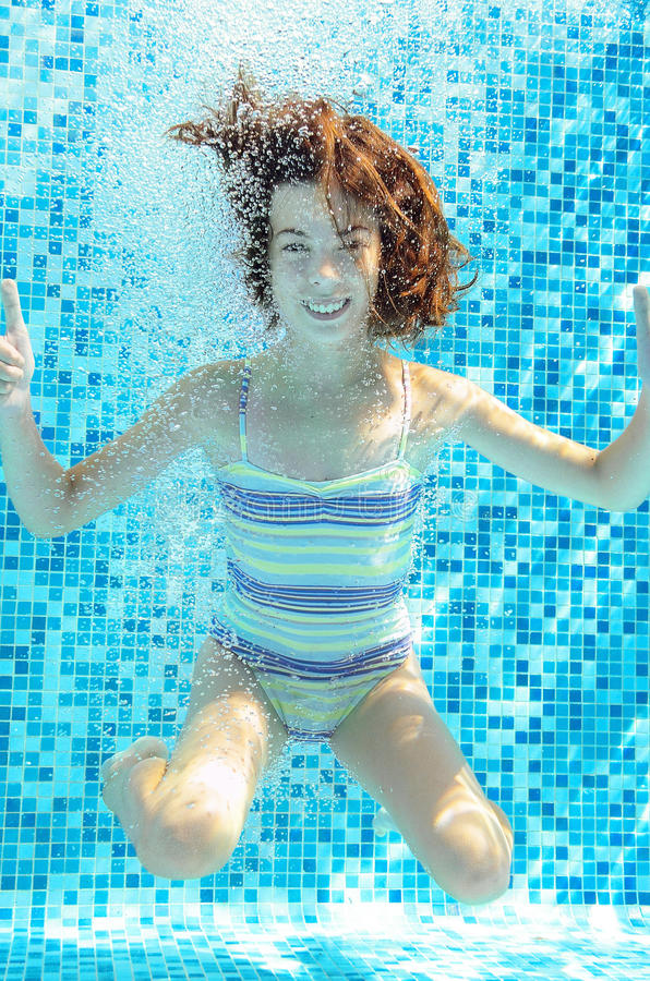 Flickan hoppar, dyker och simmar i den undervattens- pölen, det lyckliga aktiva barnet har gyckel under vatten, ungesport arkivbild