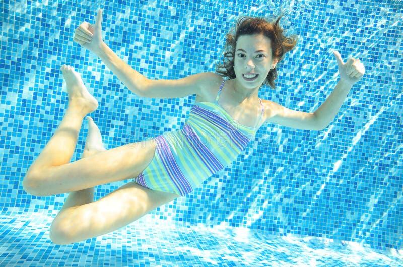 Flickan hoppar, dyker och simmar i den undervattens- pölen, det lyckliga aktiva barnet har gyckel under vatten, ungesportnolla royaltyfria bilder