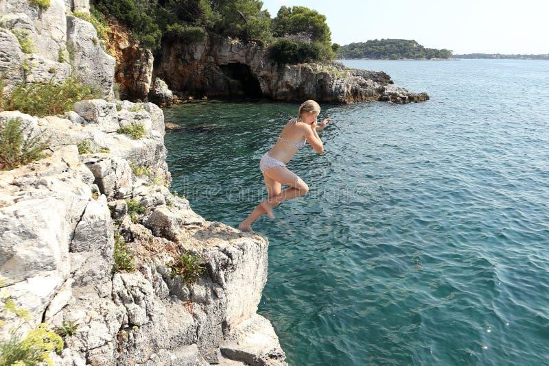 Flickan hoppar från en klippa arkivfoton