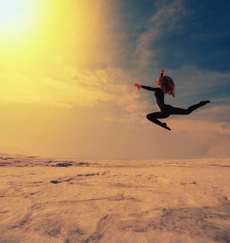 Flickan hoppar högt i den härliga ställingen arkivfoton