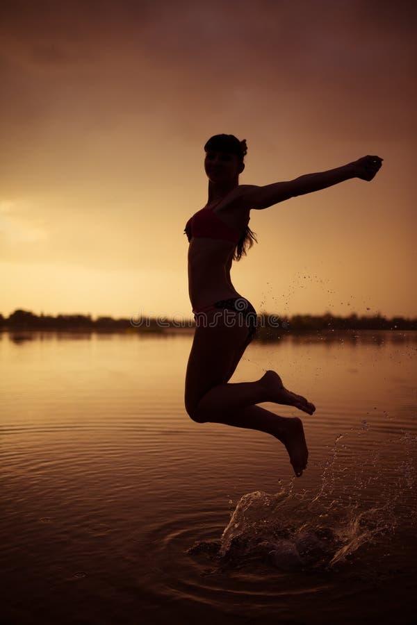 Flickan hoppar i floden på solnedgången arkivbild