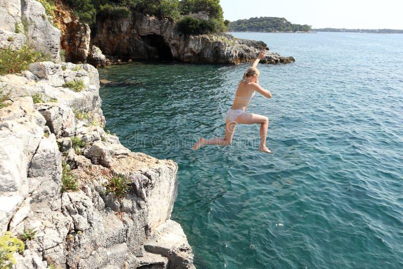 Flickan hoppar i vatten arkivbild