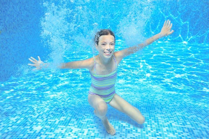 Flickan hoppar och simmar i den undervattens- pölen, det lyckliga aktiva barnet har gyckel under vatten fotografering för bildbyråer