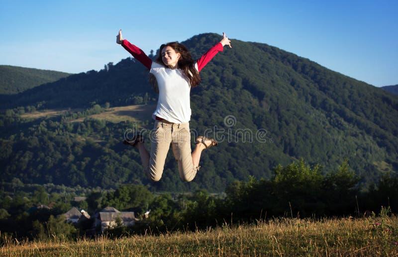 Flickan hoppar på en bakgrund av berg fotografering för bildbyråer