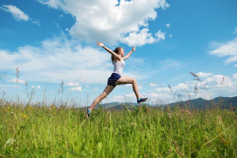 Flickan hoppar på ett grönt gräs royaltyfri fotografi