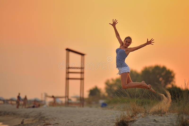 Flickan hoppar på stranden