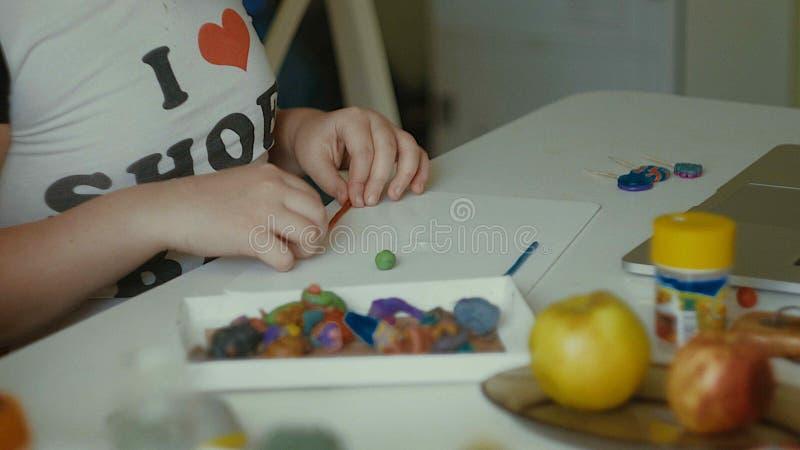Flickan hugger plasticinestatyetter på tabellen royaltyfri fotografi
