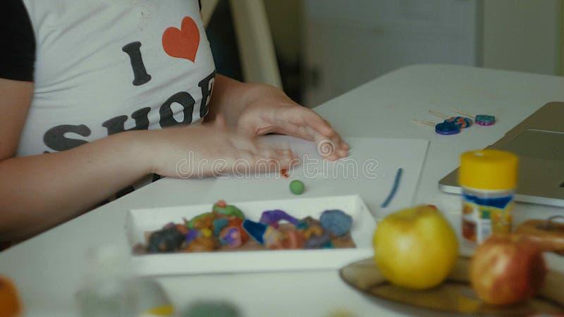 Flickan hugger plasticinestatyetter på tabellen royaltyfria foton