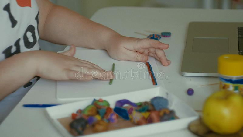 Flickan hugger plasticinestatyetter på tabellen royaltyfri foto