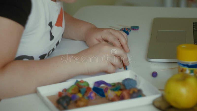Flickan hugger plasticinestatyetter på tabellen royaltyfria bilder