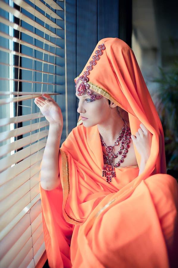 Flickan i öst beklär att stirra ut fönstret arkivfoton