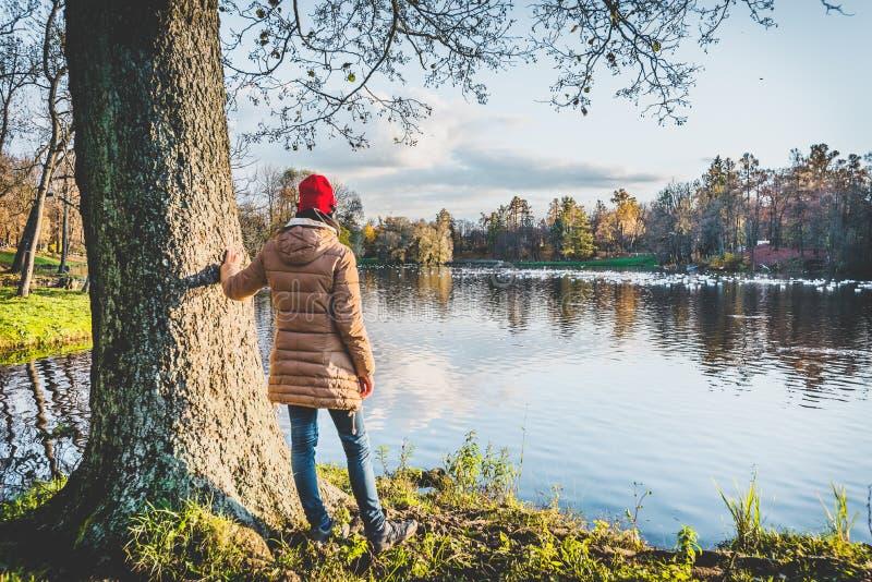 Flickan i bärande hörlurar för en röd hatt tycker om sikten av en autum royaltyfri bild