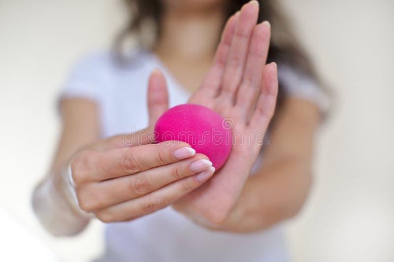 Flickan i badrummet, i en vit t-skjorta gör makeup med den rosa skönhetblandaren, kvinna rymmer skönhetsmedel för en borste, den  arkivbild