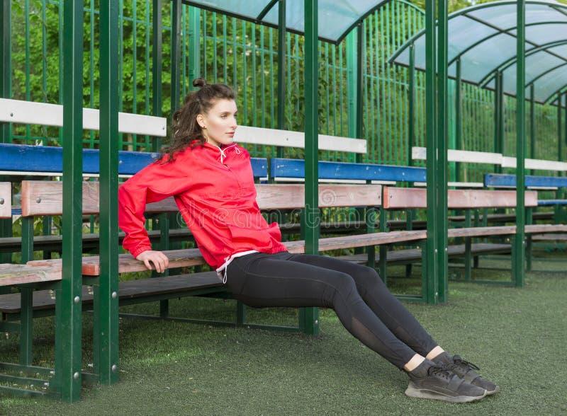 Flickan i damasker och ett rött omslag kopplas in i kondition på lekplatsen arkivfoto