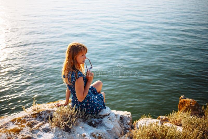 Flickan i den blåa klänningen på stenen sitter vid havet arkivfoton