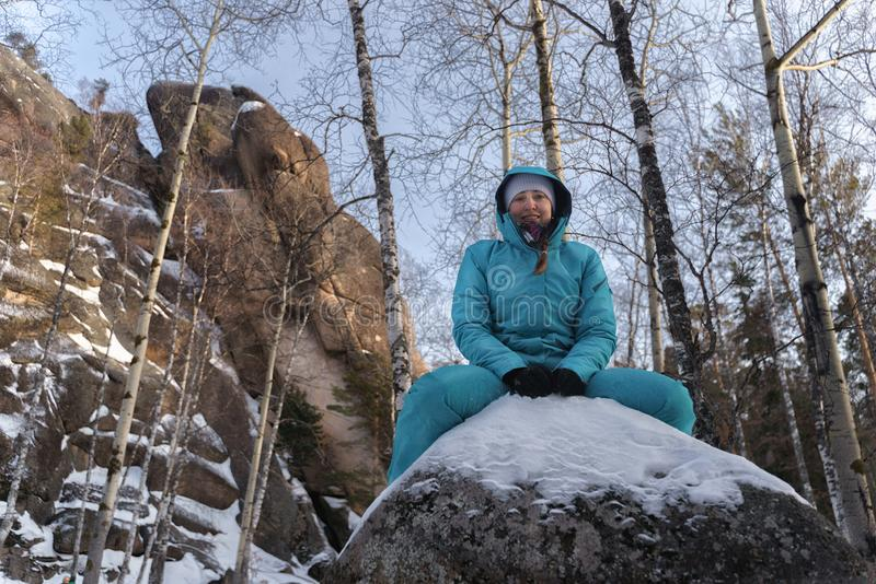 Flickan i den blåa sportswearen som sitter på en stor stenblock på naturen på bakgrunden av, vaggar i vintern royaltyfria bilder