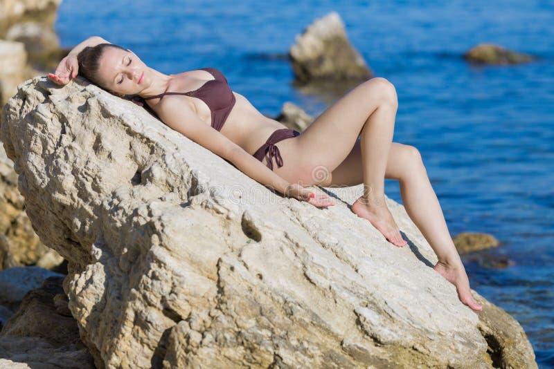 Flickan i den bruna bikinin som ligger på, vaggar med stängda ögon royaltyfria bilder