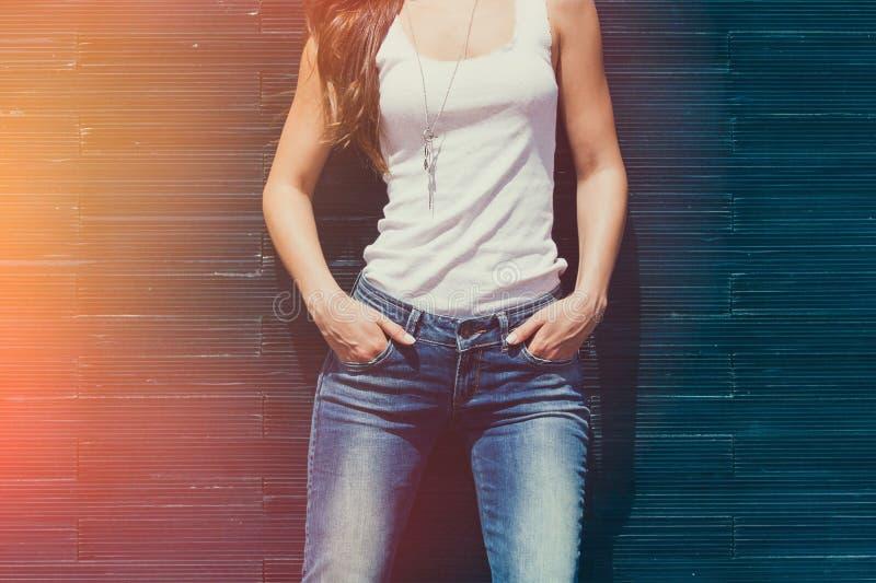 Flickan i den vita behållareskjortan och för sommardag för jeans den utomhus- mellersta kroppen lutar på den belade med tegel väg arkivbild