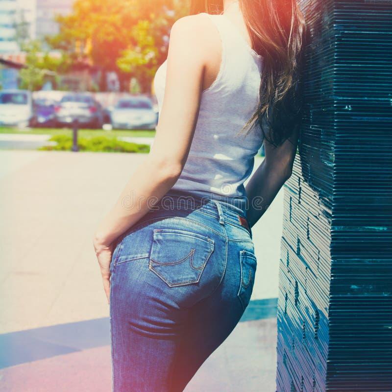 Flickan i den vita behållareskjortan och den utomhus- sommardagen för jeans lutar på belagd med tegel väggbaksidasikt arkivfoton