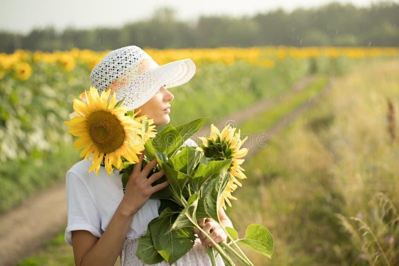 Flickan i den vita klänningen och den vita hatten går över fältet royaltyfria foton