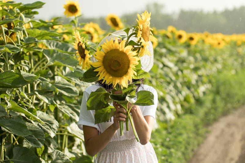 Flickan i den vita klänningen och den vita hatten går över fältet fotografering för bildbyråer