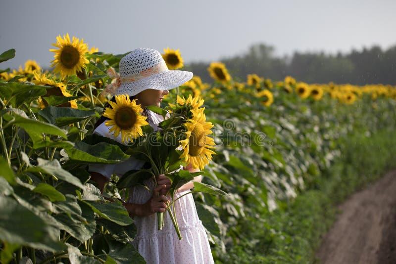 Flickan i den vita klänningen och den vita hatten går över fältet royaltyfri foto