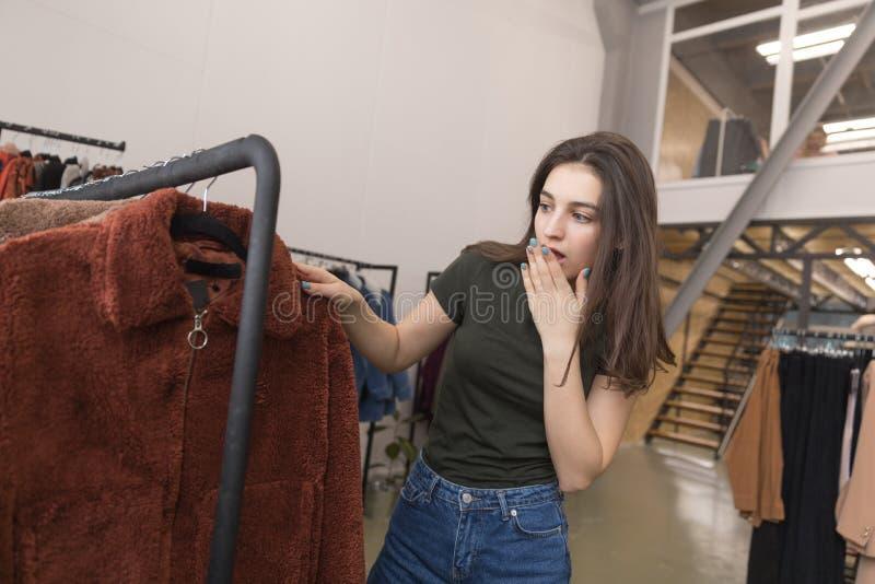 Flickan i det bekläda lagret väljer ett nytt pälslag royaltyfri fotografi
