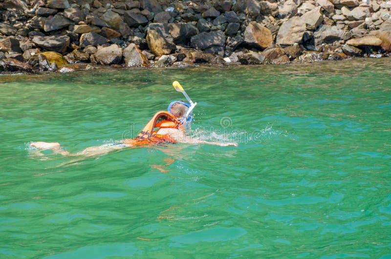 Flickan i dykar för en maskering under vatten som håller ögonen på den undervattens- världen arkivbilder