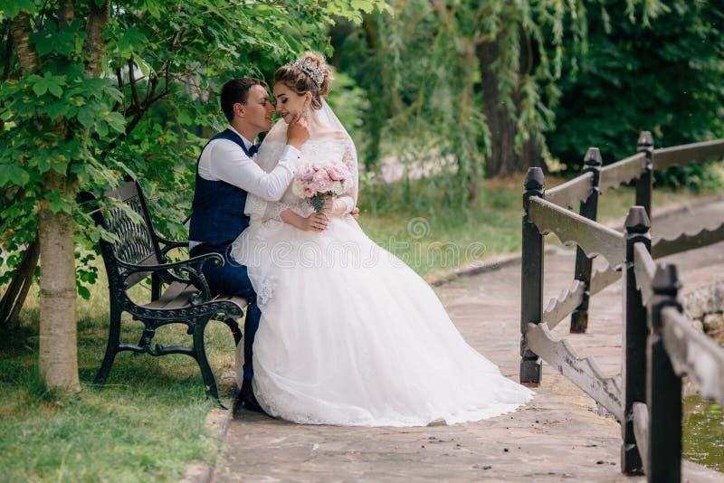 Flickan i en överdådig bröllopsklänning sitter på varven för man` s och vänder försiktigt till honom Endast få gift och tyck om d royaltyfri foto