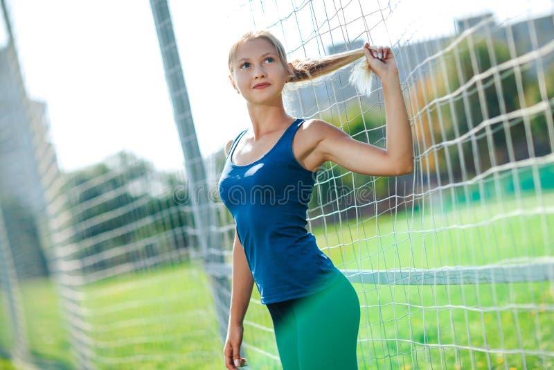 Flickan i en blå skjorta och damasker rymmer hennes hår i hennes hand, står nära ett fotbollmål på stadion på solnedgången En fli arkivfoton