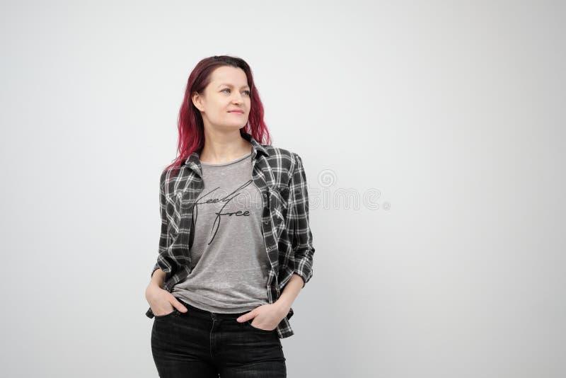 Flickan i en grå skjorta för pläd på en vit bakgrund med färgat rött hår royaltyfria foton