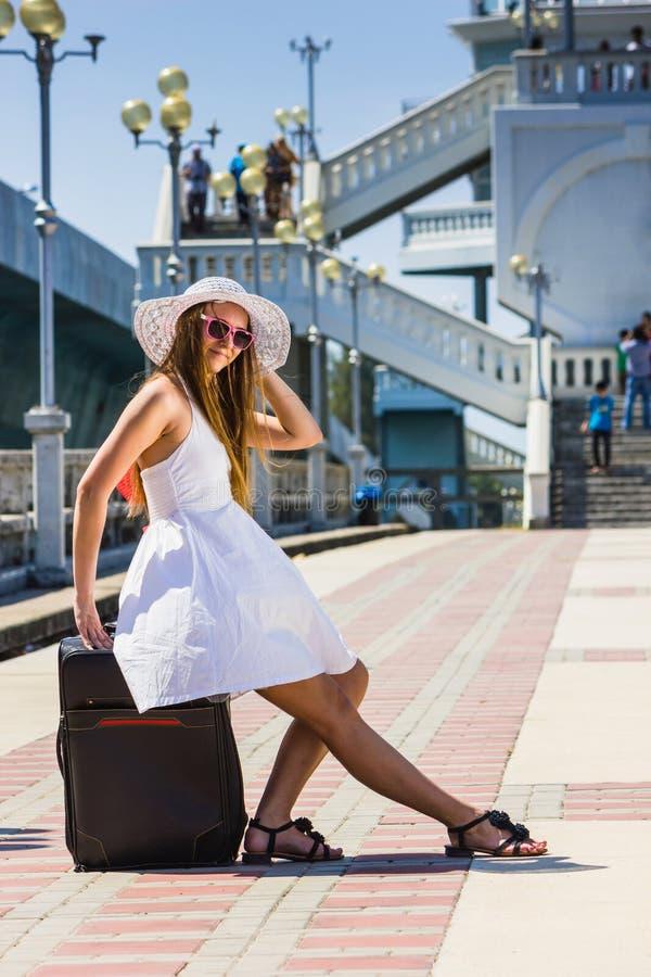 Flickan i en hatt med en resväska som går på, vilar arkivfoton