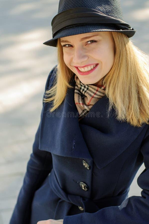 Flickan i en hatt med ett guld- hår skrattar glatt arkivfoto