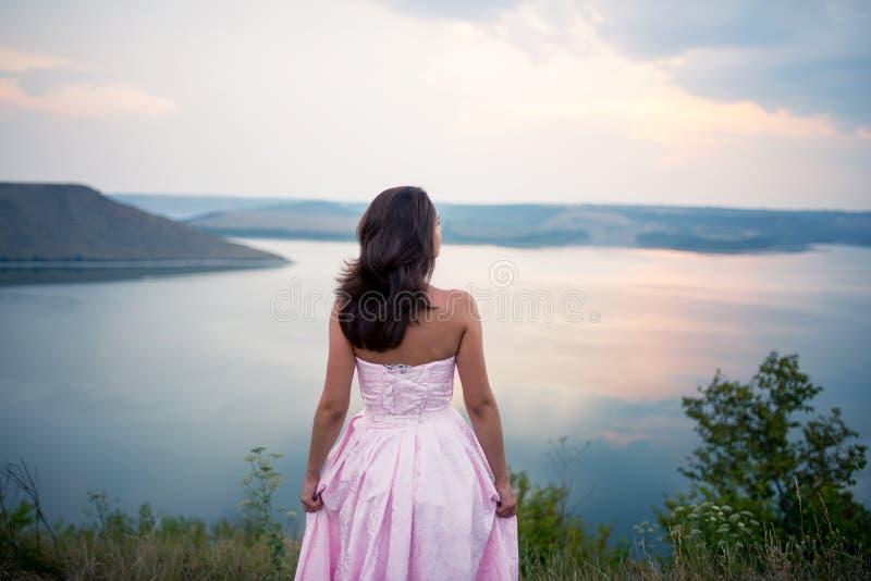 Flickan i en klänning ser horisonten av floden arkivbild