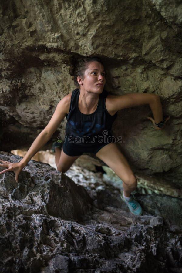 Flickan i en mörk grotta arkivbild