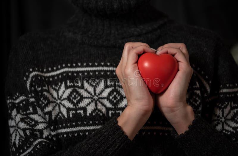 Flickan i en mörk vintertröja rymmer stor röd hjärta i hand arkivbild