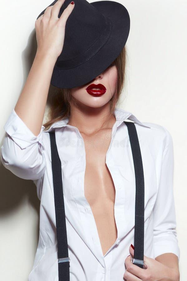 Flickan i en mans skjorta med hängslen royaltyfri foto