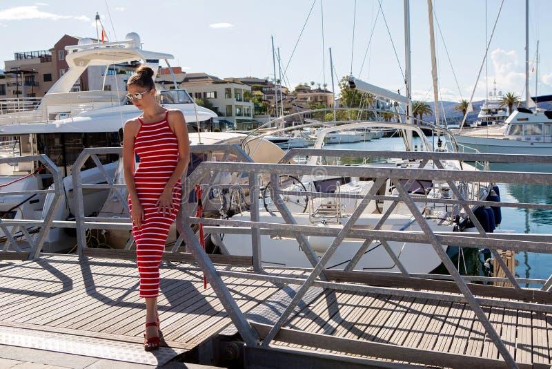 Flickan i en röd randig klänning står på yachten arkivbild