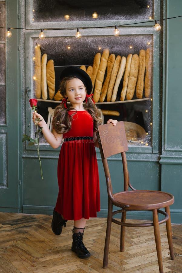 Flickan i en röd sammetskklädd som håller en röd ros och står nära en stol på bageriet arkivfoto