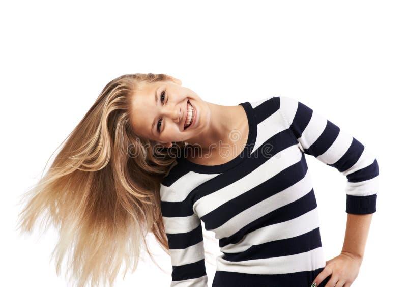 Flickan i en randig tröja vrider hår fotografering för bildbyråer