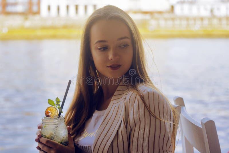 Flickan i en restaurang på skeppet nära floddrinkmojitoen Brunettleende- och drinkmojito i en exponeringsglaskrus arkivbilder