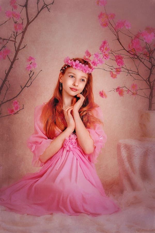Flickan i en rosa klänning och rosa färgkrans arkivbilder