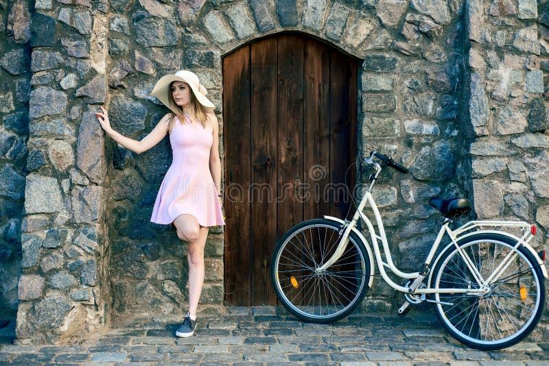 Flickan i en rosa klänning och en sugrörhatt står bredvid en texturerad sten, gammal vägg med en trädörr arkivfoton