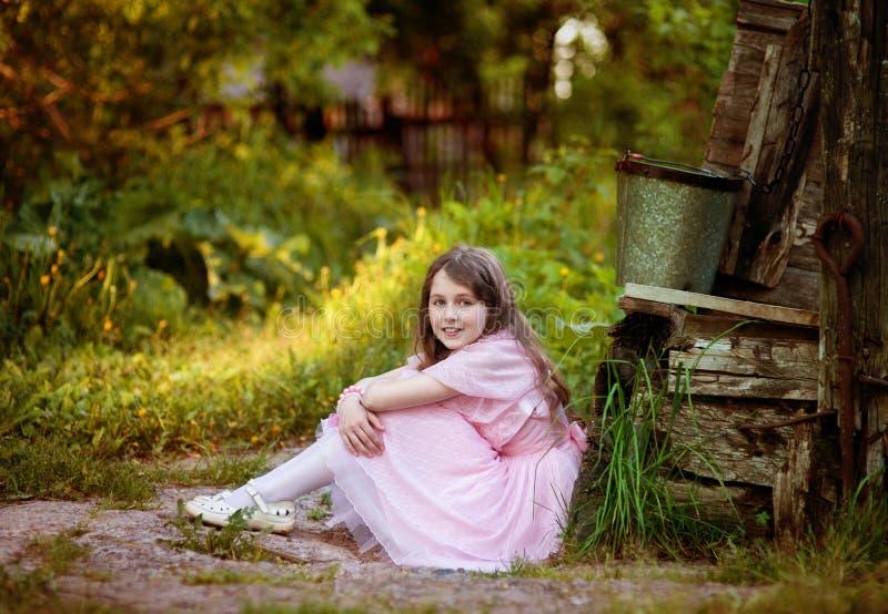 Flickan i en rosa klänning sitter i en sommarträdgård på en gammal brunn arkivbild